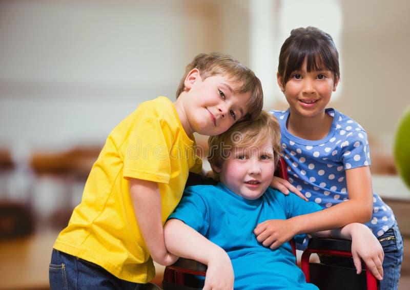 Niepełnosprawna chłopiec w wózku inwalidzkim z przyjaciółmi w szkolnej sala lekcyjnej zdjęcia stock