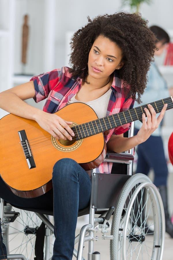 Niepełnosprawna dziewczyna bawić się gitarę zdjęcia royalty free