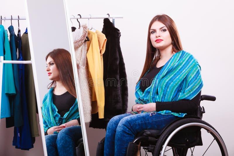 Niepełnosprawna dziewczyna na wózka inwalidzkiego wybierać odziewa fotografia royalty free