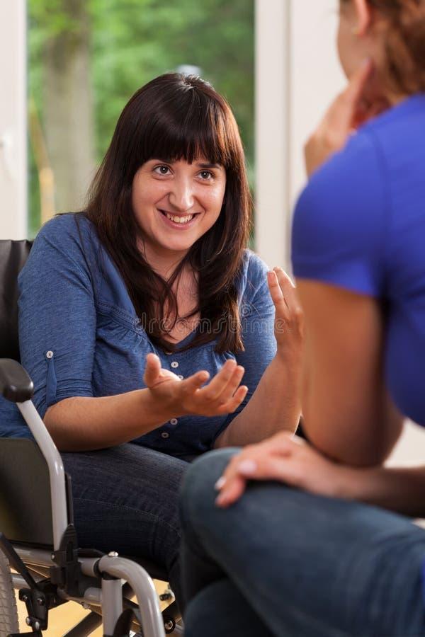 Niepełnosprawna dziewczyna opowiada z jej przyjacielem zdjęcie royalty free