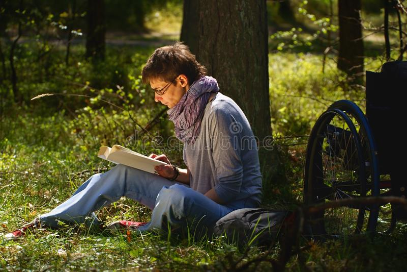 Niepełnosprawna kobieta czyta książkę w lesie, wózek inwalidzki obraz stock