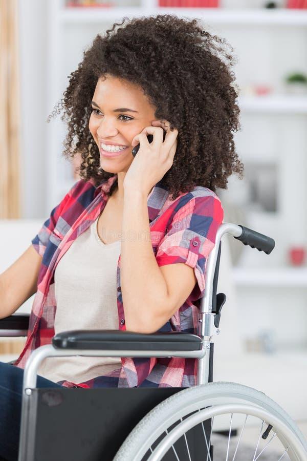 Niepełnosprawna kobieta na wózku inwalidzkim używać Mobil telefon obrazy stock