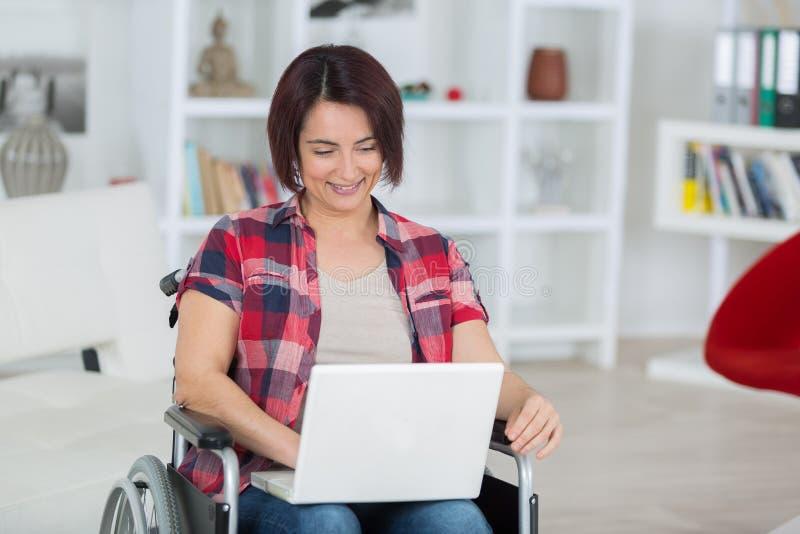 Niepełnosprawna kobieta na wózku inwalidzkim z laptopem w domu fotografia royalty free