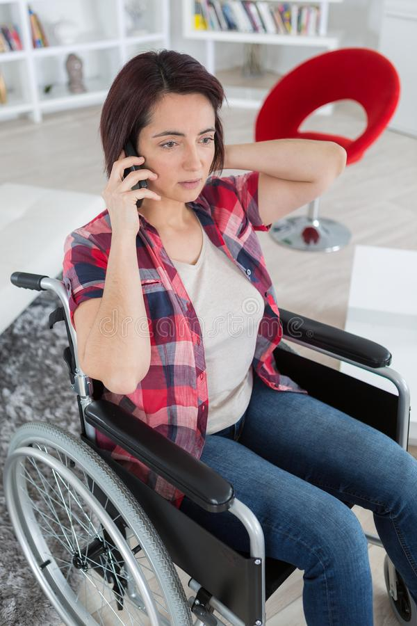 Niepełnosprawna kobieta w wózku inwalidzkim na telefonie komórkowym obrazy stock