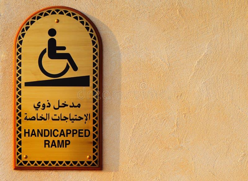 Niepełnosprawna plakieta w języku arabskim i angielszczyzny przy wejściem meczet obraz royalty free