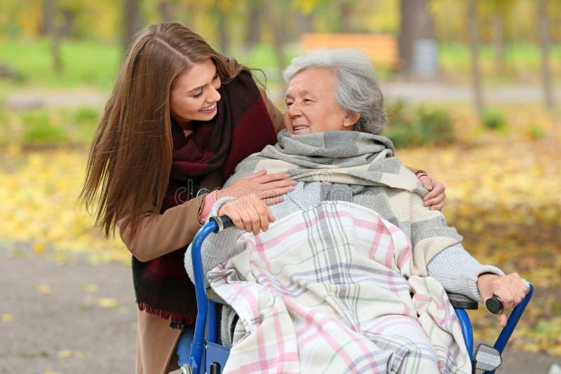 Niepełnosprawna starsza kobieta i potomstwo opiekun fotografia stock