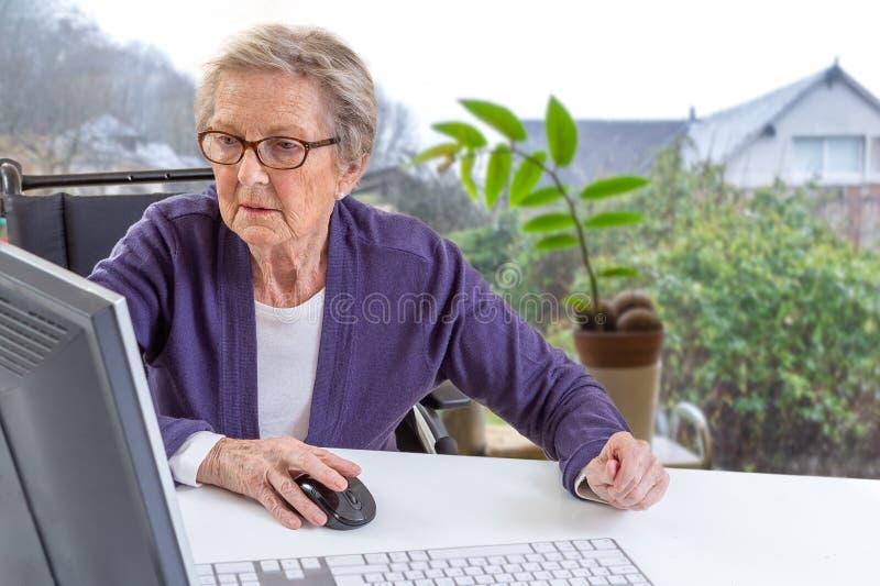 Niepełnosprawna Starsza kobieta konsultuje zdrowie lekarkę z pastylki komputerowym obsiadaniem na wózku inwalidzkim obrazy royalty free