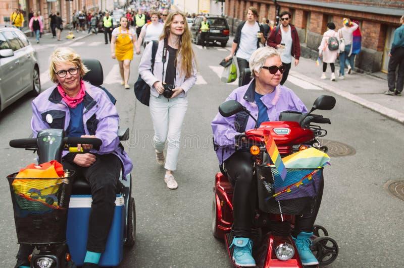 Niepełnosprawne kobiety w elektrycznym nieważnym wózku inwalidzkim na Helsinki szczycą się festiwal na ulicie obrazy royalty free