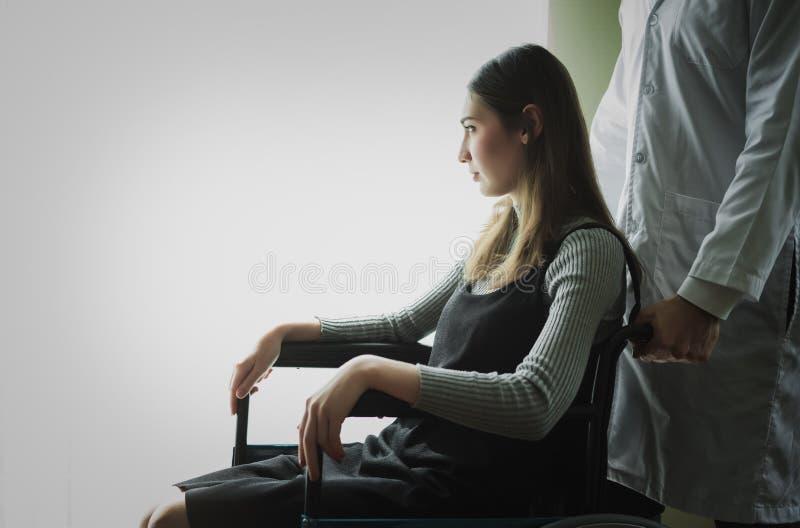 Niepełnosprawnej kobiety samotny cierpliwy obsiadanie przy wózkiem inwalidzkim w szpitalu r fotografia royalty free