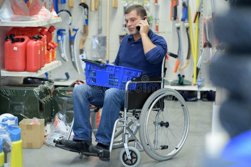 Niepełnosprawni pracownika kupienia narzędzia w sklepie fotografia stock