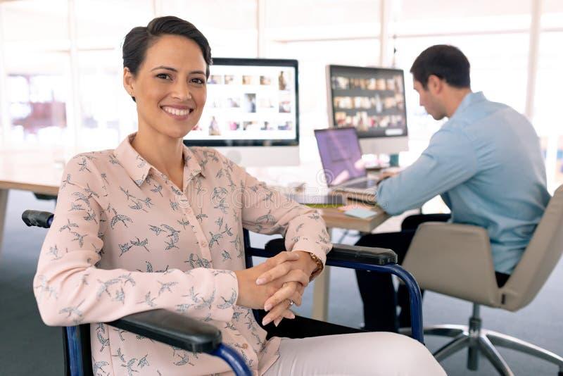 Niepełnosprawny żeński projektant grafik komputerowych patrzeje kamerę w nowożytnym biurze obraz royalty free