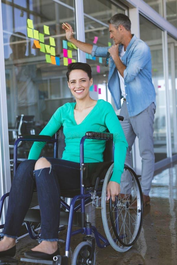 Niepełnosprawny bizneswoman patrzeje kamerę podczas gdy męski kierownictwo pisze na kleistych notatkach zdjęcie stock
