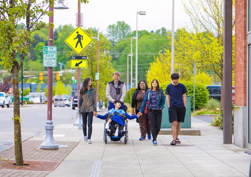 Niepełnosprawny chłopiec na wózku inwalidzkim w mieście z rodziną i opiekunem zdjęcia royalty free