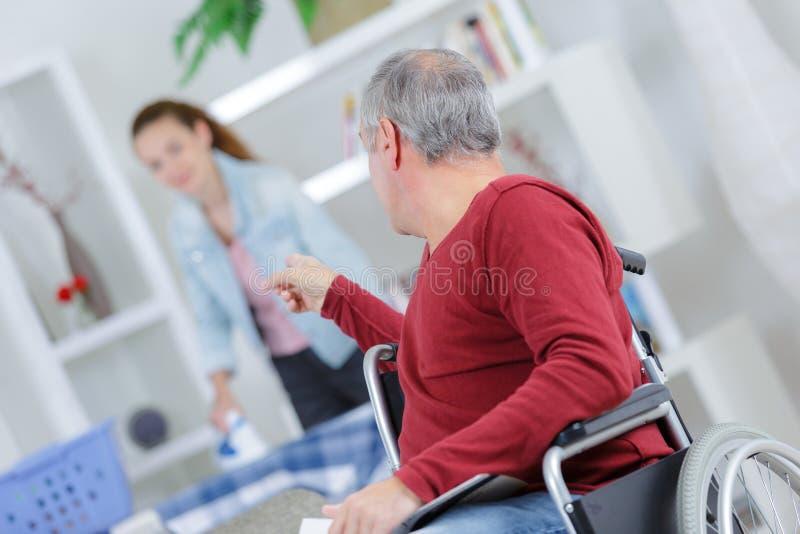 Niepełnosprawny cierpliwy wskazywać przy pięknym opieka zdrowotna pracownikiem obrazy stock