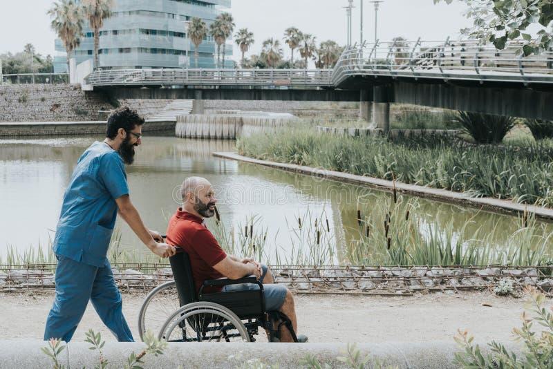 niepełnosprawny mężczyzna który iść w wózku inwalidzkim odtransportowywa lekarką fotografia stock
