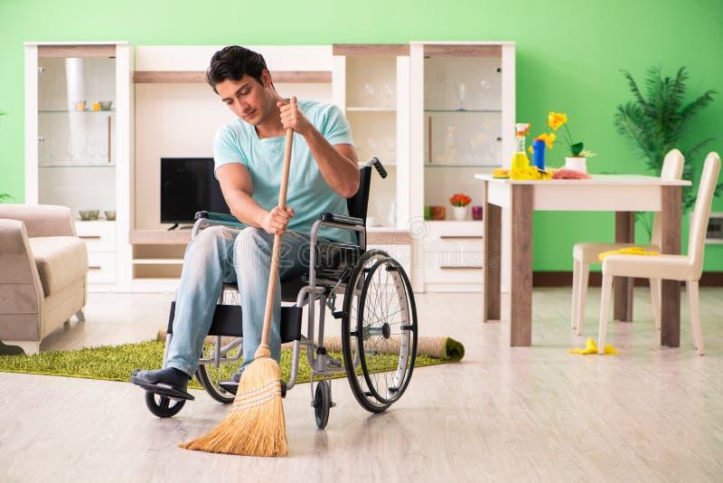 Niepełnosprawny mężczyzna na wózka inwalidzkiego cleaning domu zdjęcie royalty free