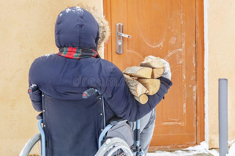 Niepełnosprawny mężczyzna na wózku inwalidzkim blisko drzwi z łupką notuje zdjęcie royalty free
