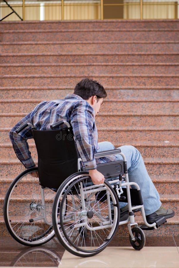 Niepełnosprawny mężczyzna na wózku inwalidzkim ma kłopot z schodkami zdjęcia royalty free