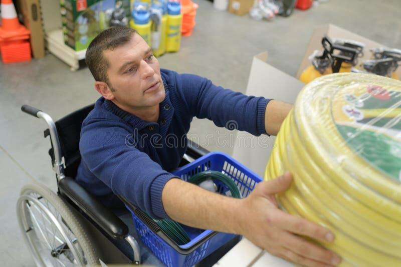 Niepełnosprawny mężczyzna ono zmaga się dosięgać węża elastycznego przy ogrodnictwo sklepem obraz stock
