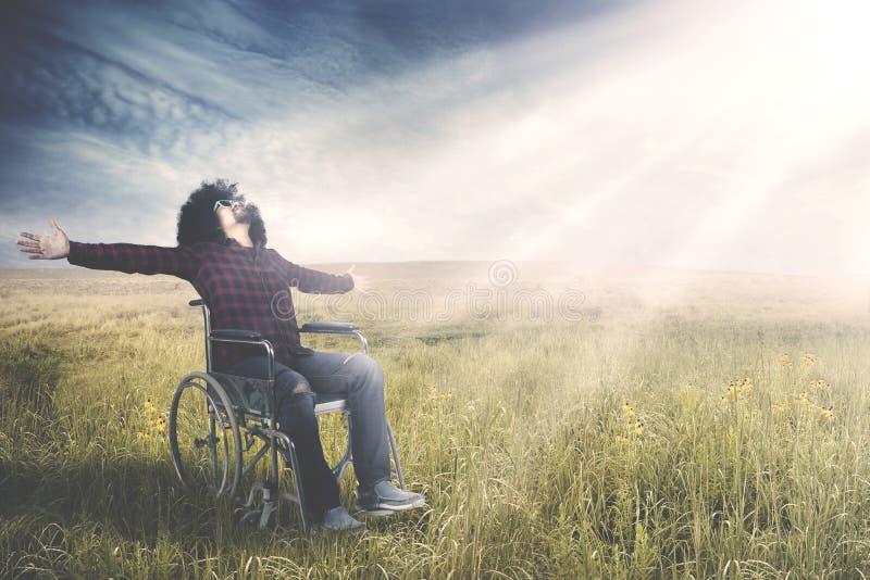 Niepełnosprawny mężczyzna siedzi na wózku inwalidzkim przy polem obraz royalty free
