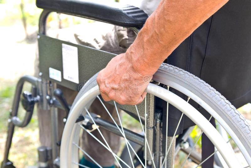 Niepełnosprawny mężczyzna siedzi w wózku inwalidzkim, Trzyma jego ręki na kole Foru poj?cia ludzie obrazy royalty free