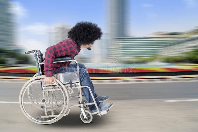 Niepełnosprawny mężczyzna siedzi w wózku inwalidzkim z szybkim ruchem obrazy royalty free