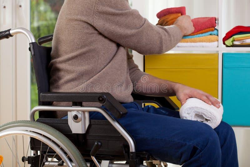 Niepełnosprawny mężczyzna sortuje ręczniki fotografia royalty free