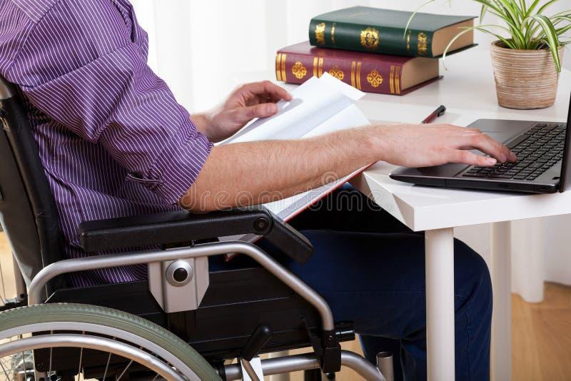 Niepełnosprawny mężczyzna studiuje w domu zdjęcia royalty free