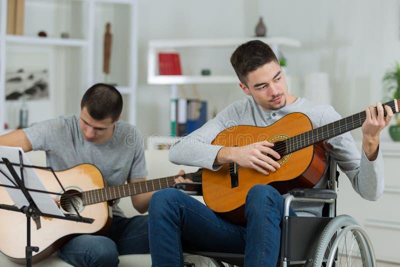 Niepełnosprawny mężczyzna w wózku inwalidzkim bawić się gitarę z przyjacielem obrazy royalty free