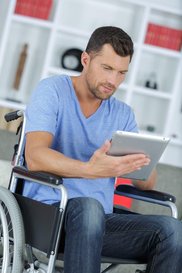 Niepełnosprawny mężczyzna W wózku inwalidzkim Używać Cyfrowej pastylkę W Domu zdjęcia royalty free
