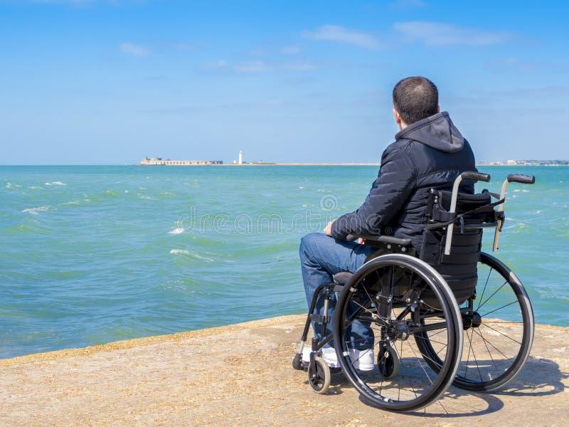 Niepełnosprawny młodego człowieka obsiadanie w wózku inwalidzkim i spojrzenia przy morzem obrazy royalty free