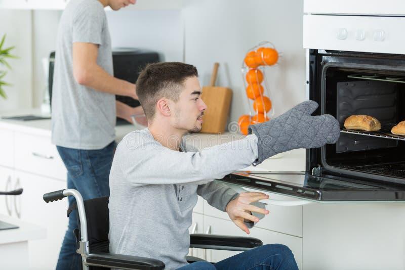 Niepełnosprawny młody człowiek w wózku inwalidzkim otwiera piekarnika przygotowywać jedzenie zdjęcie stock