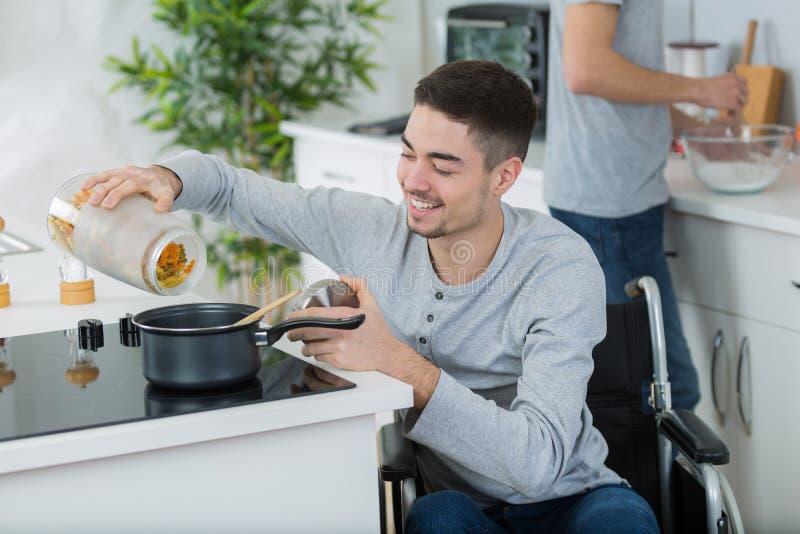 Niepełnosprawny młody człowiek w wózku inwalidzkim w kuchni zdjęcia royalty free
