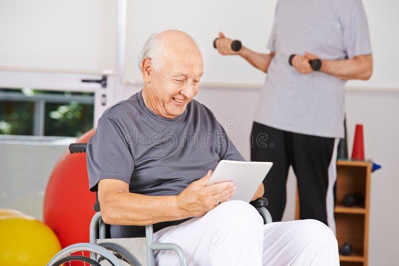 Niepełnosprawny stary człowiek w wózku inwalidzkim z pastylka pecetem obraz royalty free