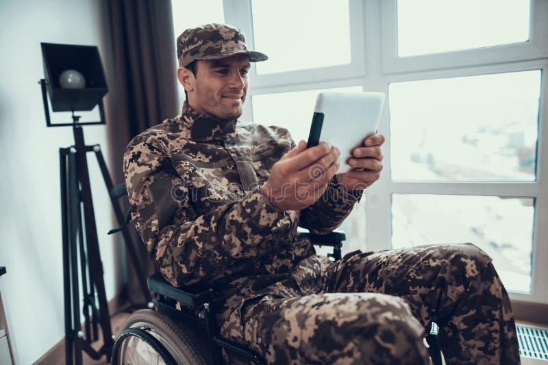 Niepełnosprawny wojskowy Używa pastylkę w wózku inwalidzkim fotografia royalty free