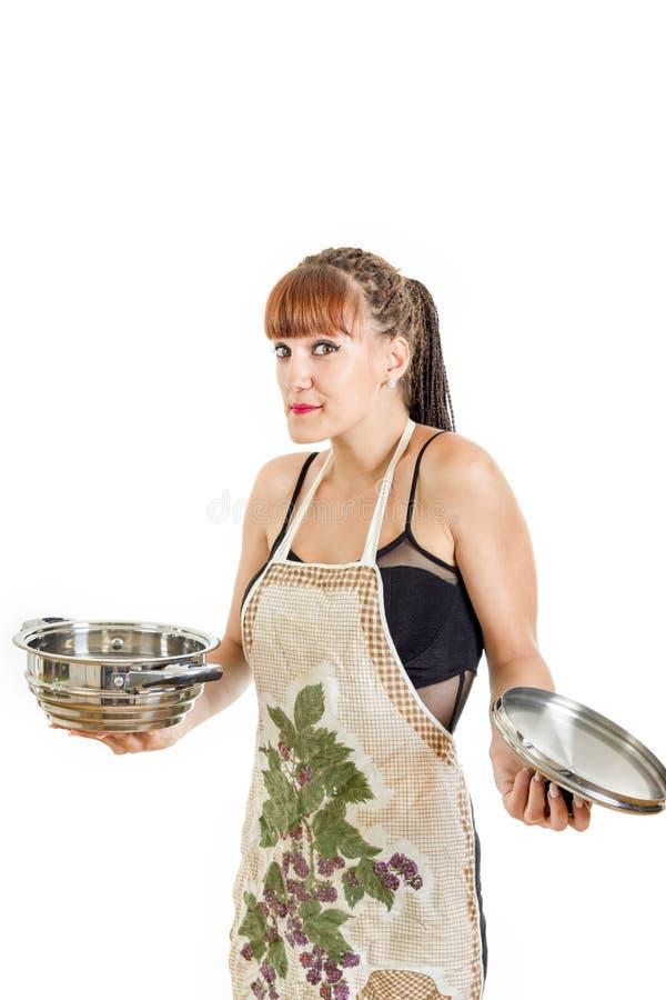 Niepewna dziewczyna nowa w kuchni z garnkiem jest ubranym fartucha zdjęcie royalty free
