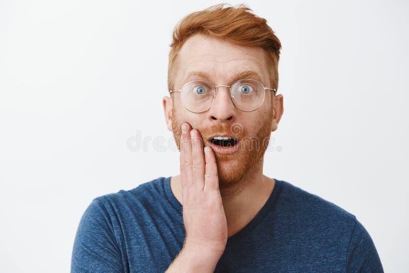 Niepewny śliczny rudzielec mężczyzna w szkłach no expact buziak w policzku od kochającej kobiety na dacie, dotyka twarz i gapić s zdjęcia royalty free