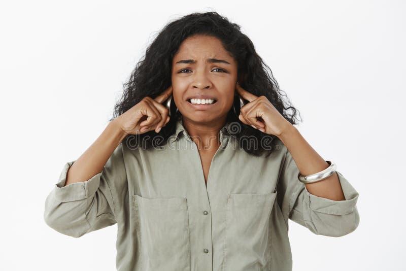 Niepewny podrażnionego, nieradego amerykanin afrykańskiego pochodzenia żeński uczeń zaciska zęby zamyka ucho z wskaźnikiem w modn obrazy stock