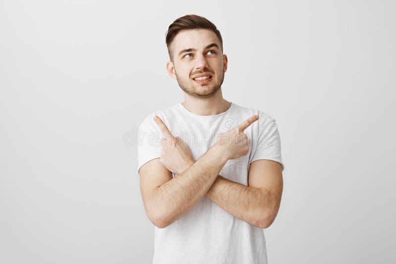 Niepewny zmartwiony facet czuje nerwowy robi mylny decyzi stać intensywny nad szarym tłem w białym koszulki skrzyżowaniu obrazy royalty free