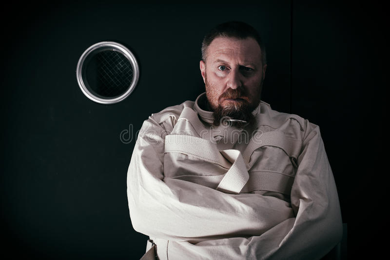 Niepoczytalny mężczyzna w komórce jest ubranym straitjacket zdjęcia stock