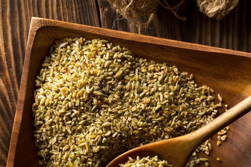 Niepoddane obróbce cieplnej, surowe, liściaste lub firik, z ziaren pszenicy palonej, na drewnianej płytce z łyżką drewnianą na br obrazy stock