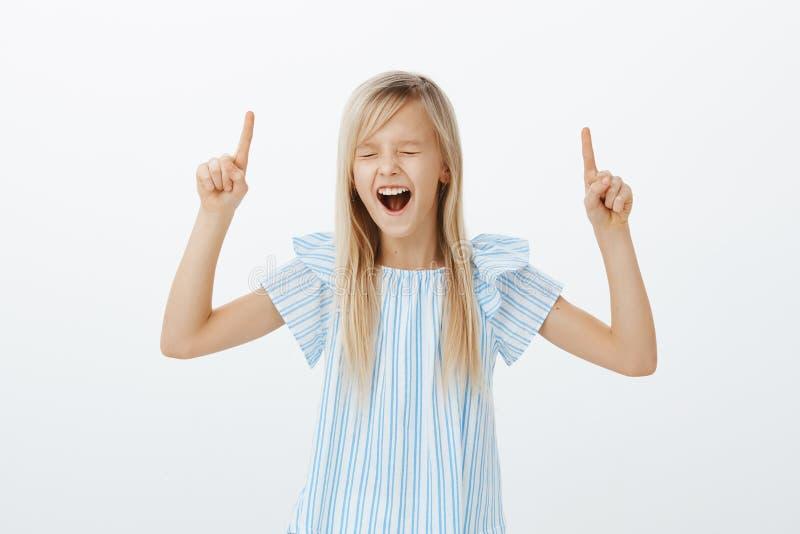 Niepodporządkowana energiczna mała blond dziewczyna podnosi palce wskazujących, wskazuje up, wrzeszczy out głośnego z i krzyczy, obraz royalty free