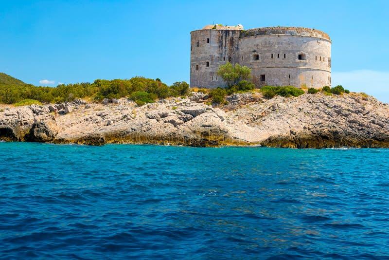 Nieprawdopodobny seascape Stary wierza na skalistym brzeg morzem, Boka-Kotor zatoka, zdjęcia stock