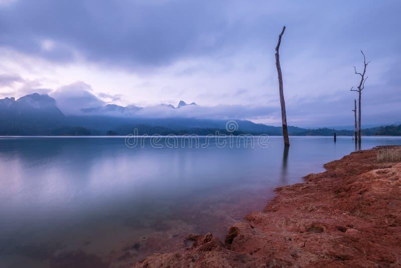 Nieprawdopodobny widok Cheow Lan jezioro z zmierzchu niebem i dowód preexisting dżungla las który zalewał gdy Rajjaprabha fotografia stock