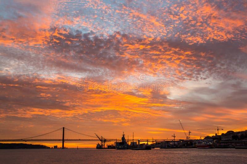 Nieprawdopodobny Złoty zmierzch nad rzeką Tagus, Bridżowy Kwiecień 25 i Lisbon port, Portugalia zdjęcia stock