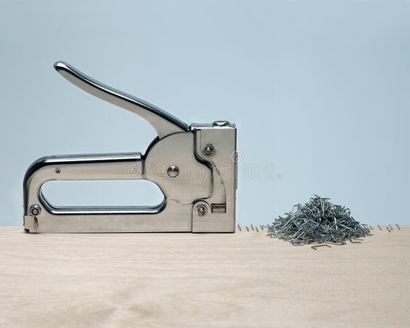 Nieprawidłowe działanie pistoletu zszywającego, tworzące precyzyjny rząd i duży stos zszywek na powierzchni drewna zdjęcie royalty free