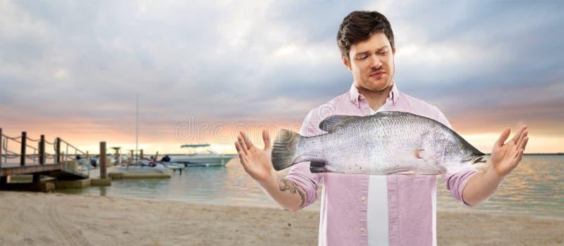 Nierad młodego człowieka seansu rozmiar ryba na plaży fotografia royalty free
