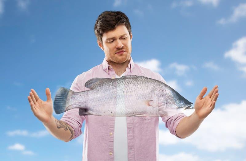 Nierad młodego człowieka seansu rozmiar ryba nad niebem obrazy stock