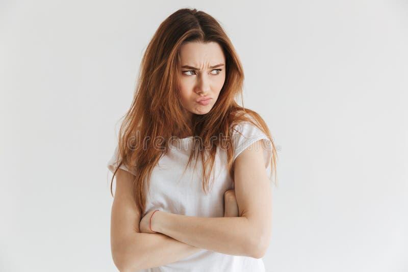 Nierada kobieta patrzeje kamerę w koszulce z krzyżować rękami obrazy stock