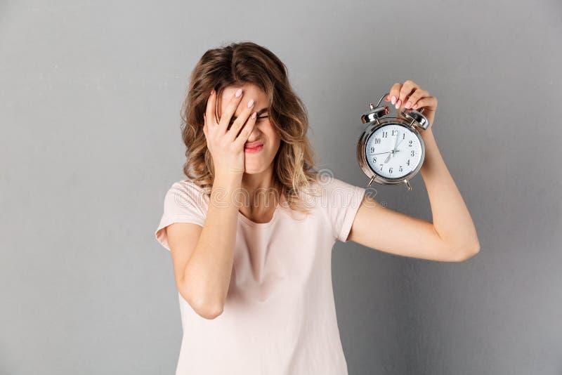 Nierada kobieta w koszulki nakrycia twarzy podczas gdy trzymający budzika zdjęcie royalty free